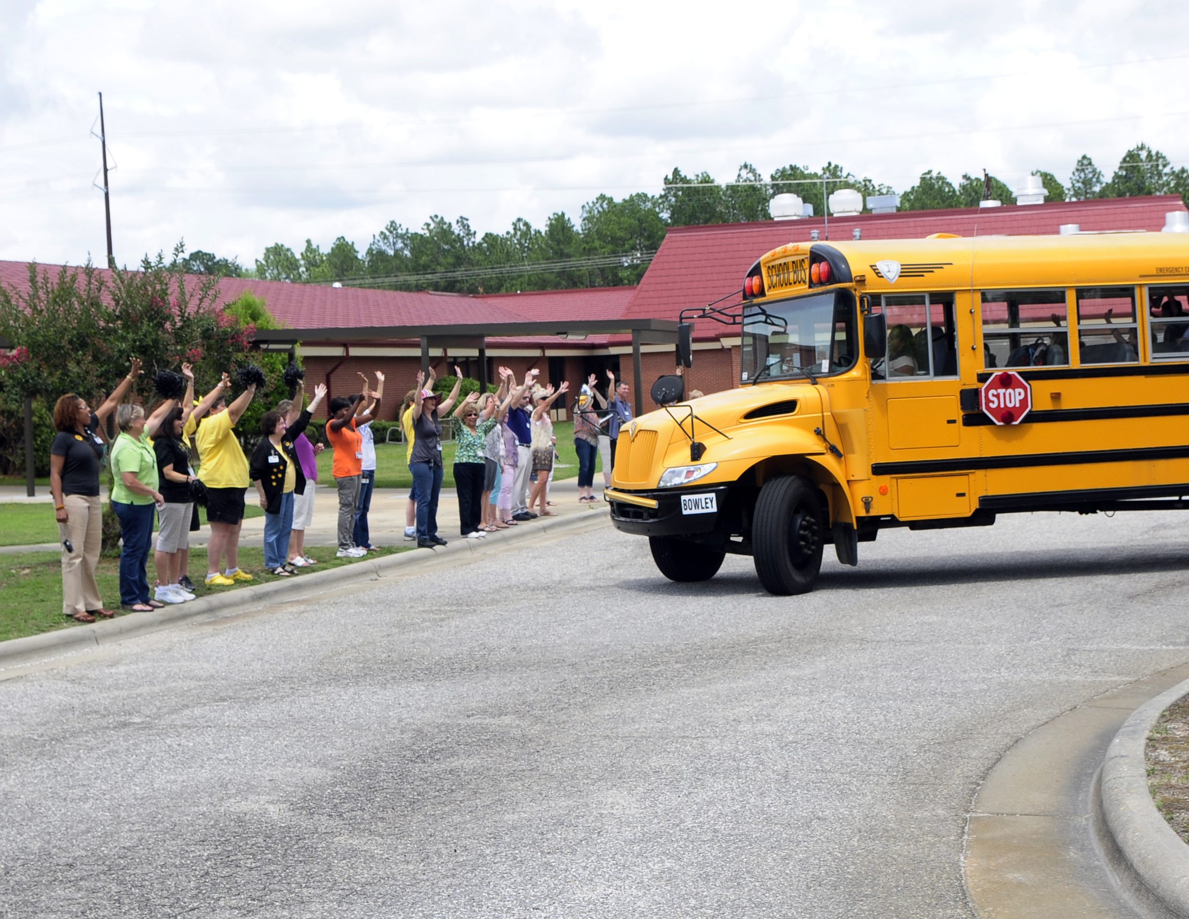 Teachers and administrative staff wave goodbye to students (Wikimedia Commons)